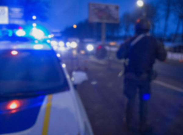 Unrecognizable blurry police car lights and police force officer on night road background.