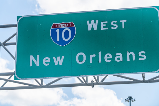Highway road i10 west interstate 10 with direction sign and text on street for New Orleans in Louisiana with symbol